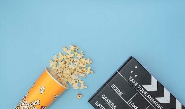 Чашка попкорна и хлопушка для кино как концепция ночи кино