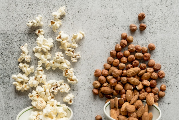 Popcorn and dry fruits fallen from bowl on concrete backdrop