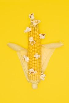 ポップコーンは、黄色の背景にトウモロコシの穂軸で爆発します。