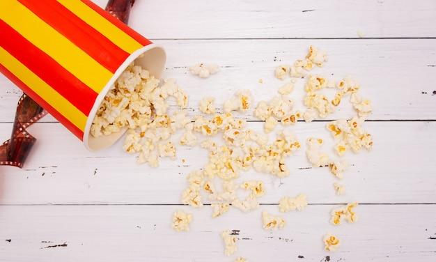 ポップコーン、白い木製の背景、上面図のフィルム。映画のコンセプト。