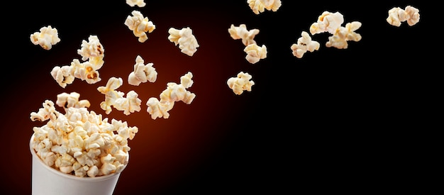 Popcorn flying out of cardboard box. isolated on black background