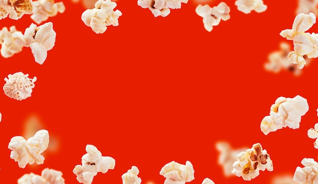 Popcorn frame, flying popcorn isolated on red background with copy space