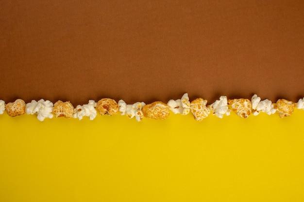 黄褐色の机の上に新鮮な塩味の甘いポップコーン