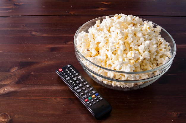 Popcorn in glass bowl and remote control