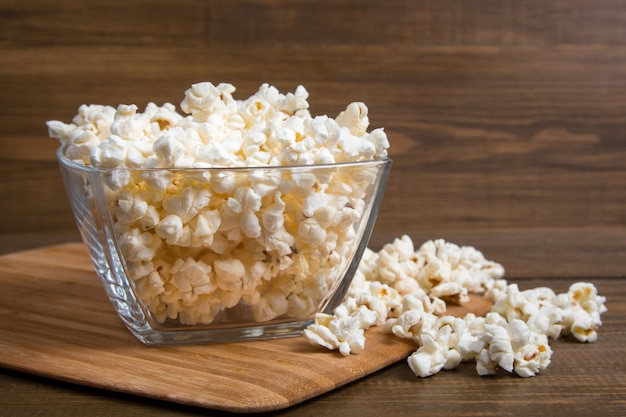 Popcorn in glass bowl on wooden