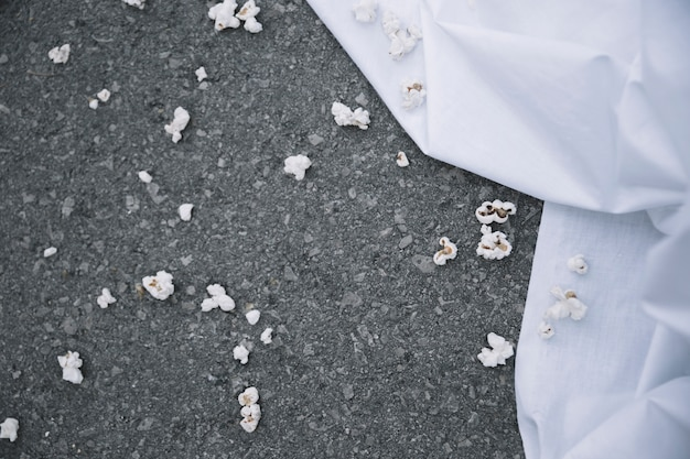 Popcorn on ground near white sheet
