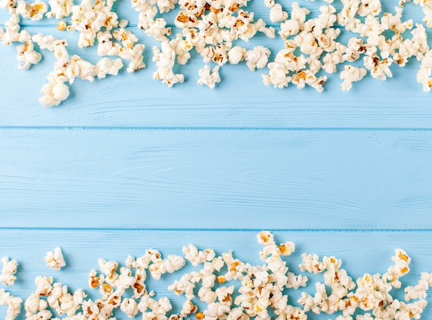 Popcorn horizontal banner. kernels lying in form of frame on blue wooden background.