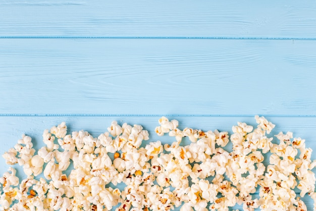 Popcorn horizontal banner. red stripped paper cup and kernels lying on blue wooden background.
