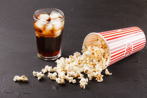 Popcorn horizontal banner. red stripped paper cup, kernels lying on dark background.