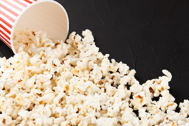 Popcorn horizontal banner. red stripped paper cup and kernels lying on dark background.