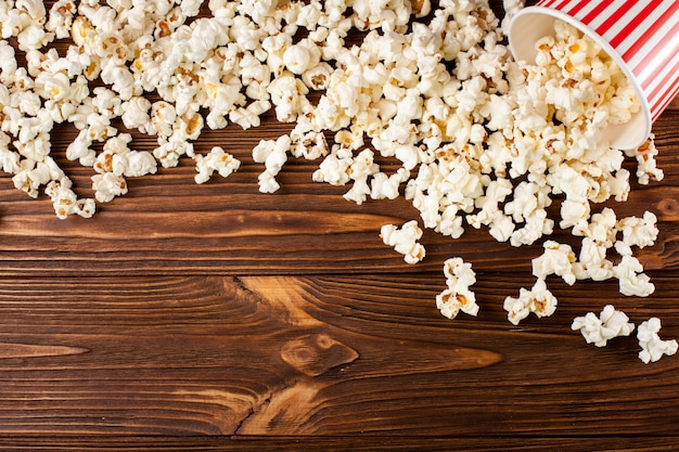 Popcorn horizontal banner. red stripped paper cup and kernels lying on dark brown wooden background.