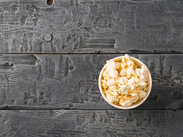Попкорн в бумажный стаканчик и на темном деревенском столе. вид сверху.