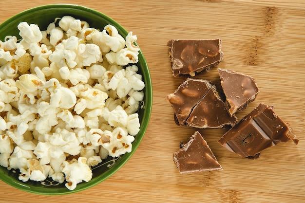 Попкорн в миске и кусочки плитки шоколада с орехами и изюмом
