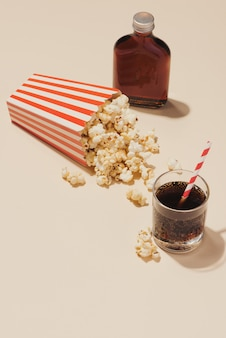 소다 한 잔과 함께 빨간색과 흰색 판지에 팝콘
