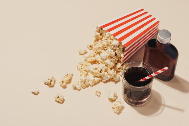 Попкорн в красно-белом картоне со стаканом газировки