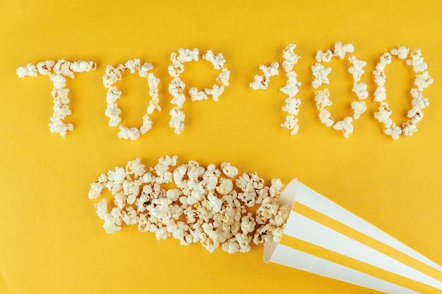 ポップコーンの碑文トップ100。ホームムービーと映画館の映画のコンセプト。コーンカーネルからのポップコーン。