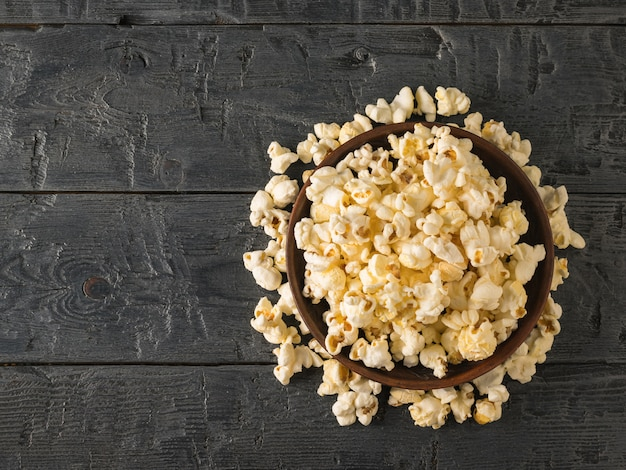 Popcorn is poured from a clay bowl on the table place for your text