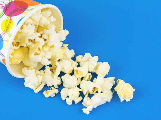 Popcorn is poured from a multi-colored paper cup on a blue table.