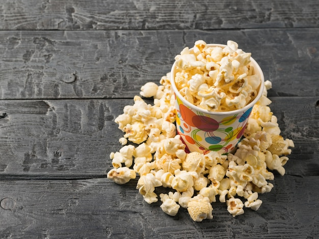 Popcorn is poured from a multi-colored paper cup on a rustic dark table.