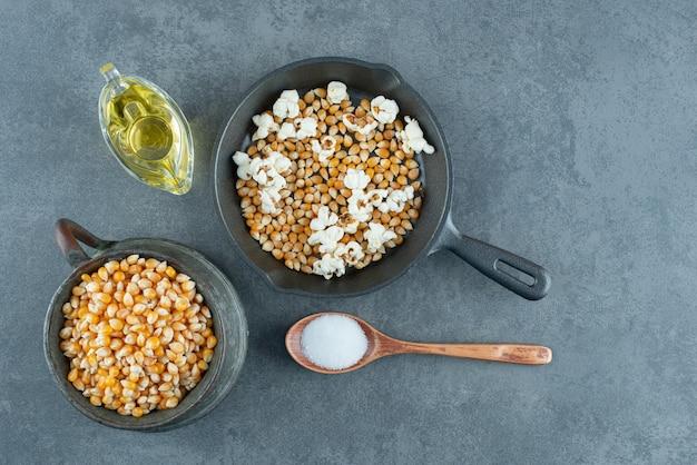 Попкорн приготовления ингредиентов, подготовленных и готовых к приготовлению на мраморном фоне. фото высокого качества