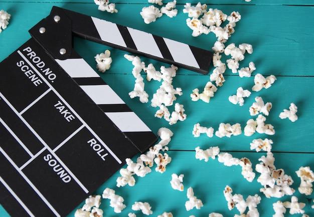 Попкорн на синем деревянном фоне, вид сверху, рядом с нумератором заслонки для фильмов