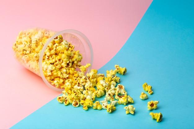 色付きの背景上のポップコーン。最小限の食品のコンセプト。エンターテイメント、映画、ビデオのコンテンツ。美学80年代と90年代のコンセプト
