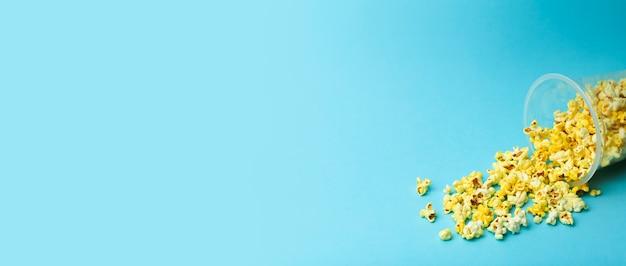 色付きのバナーの背景にポップコーン。最小限の食品のコンセプト。エンターテイメント、映画、ビデオのコンテンツ。美学80年代と90年代のコンセプト