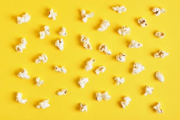 黄色の背景にポップコーン。ポップコーンパターン。上面図、コピースペース