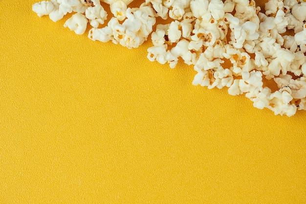 黄色の背景にポップコーン。ホームシネマと映画館の映画のコンセプト