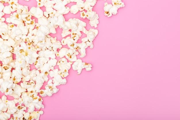 Попкорн на розовом фоне. кино или тв фон, рамка, рамка. вид сверху копирование пространства