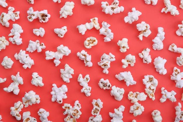 Попкорн на красном фоне вид сверху крупным планом