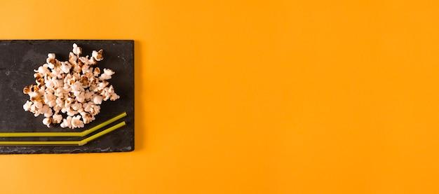 Попкорн на сланцевом подносе и соломке с содовой на желтом фоне. плоская планировка. скопируйте пространство. время домашнего кино.