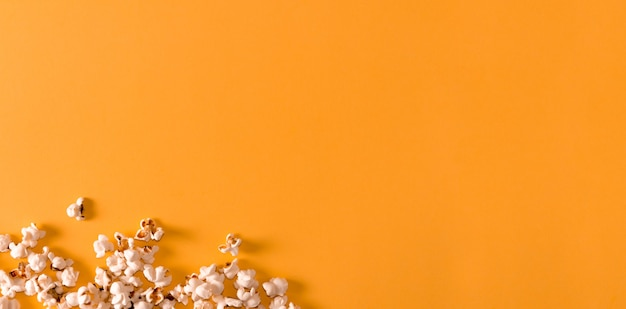 Попкорн на желтом фоне. плоская планировка. скопируйте пространство. время кино.