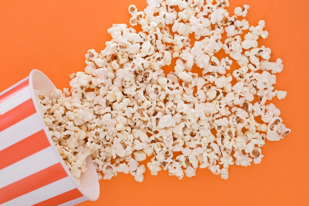 Popcorn a paper bowl to a orange background, a view from above. cup with popcorn is isolated on a orange background.