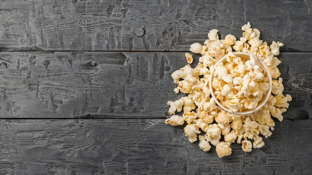 Popcorn in a paper cup and on the black wooden table. the view from the top.