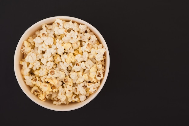 Popcorn in a paper cup is isolated on a black background, a view from above. flat lay