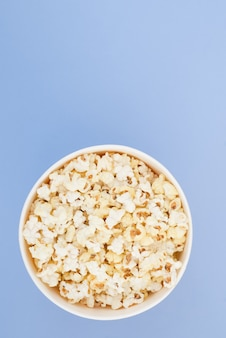 Popcorn in a paper cup is isolated on a pastel blue background, a view from above. flat lay.