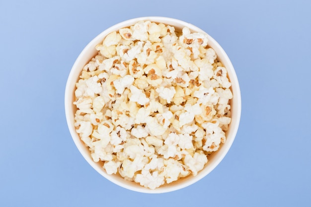 Popcorn in a paper cup is isolated on a pastel blue background, a view from above. flat lay
