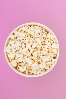Popcorn in a paper cup is isolated on a pastel pink background, a view from above. flat lay.