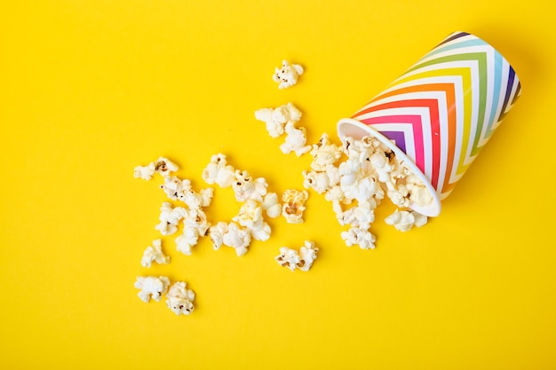 popcorn in paper cups on yellow background