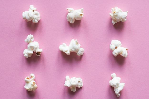 Popcorn on pink pastel background. movie snack.