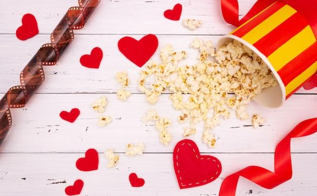 白い木製の背景にポップコーン、赤いハートとリボン。バレンタインデー、映画館。