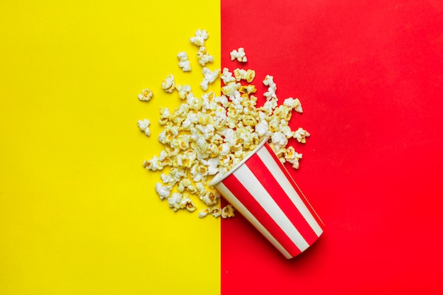 Popcorn in a red and white cardboard box on red and yellow