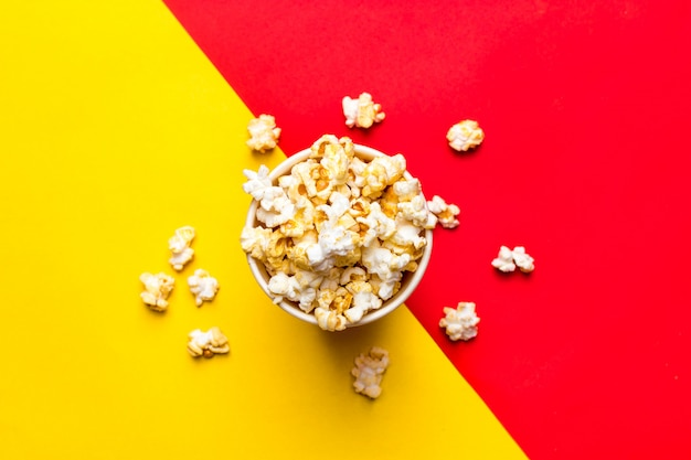 Popcorn in a red and white cardboard box on a red and yellow