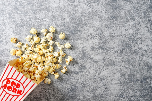 Popcorn in red and white cardboard on loft background top view flat lay