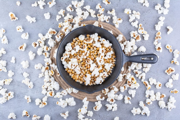 Popcorn scattered around a pan with corn grains on marble surface
