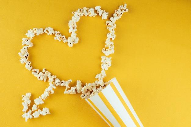 ハートの形をした黄色の背景に紙の縞模様のカップから散らばったポップコーン。ホームシネマと映画館の映画のコンセプト