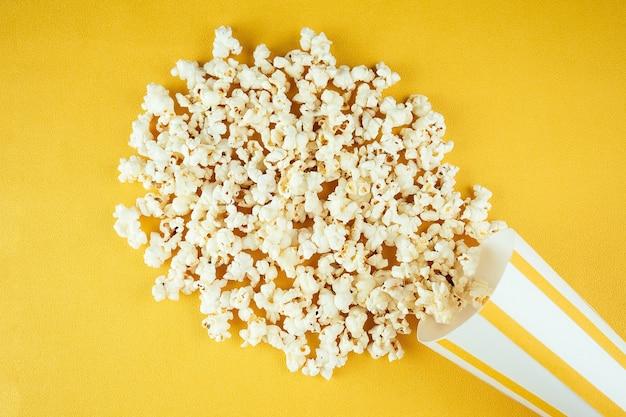 ポップコーンは、黄色の背景に紙の縞模様のガラスから散らばっています。ホームシネマと映画館の映画のコンセプト。