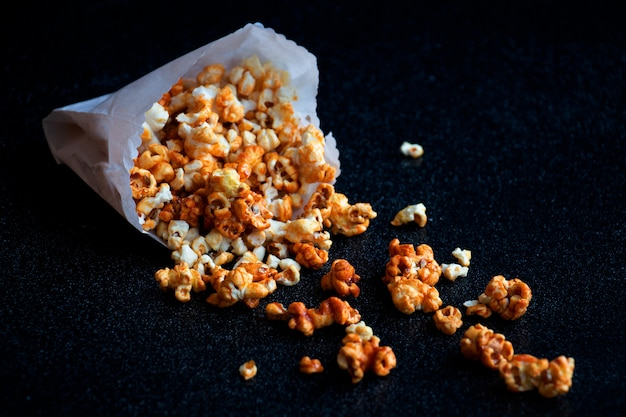Popcorn scattered from the white bag on black background