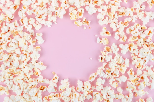 Popcorn scattered on a pink pastel background
